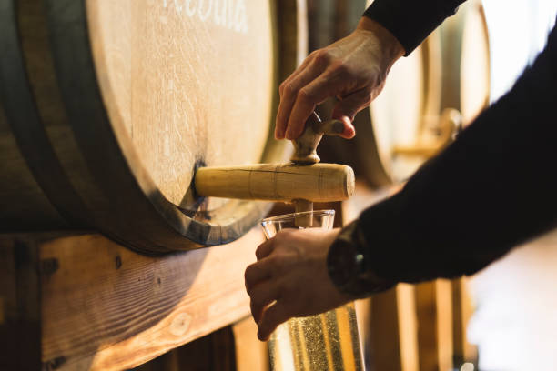 Pouring wine from wine barrel Close-up shot of man's hands pouring white wine into decanter. agricultural cooperative stock pictures, royalty-free photos & images
