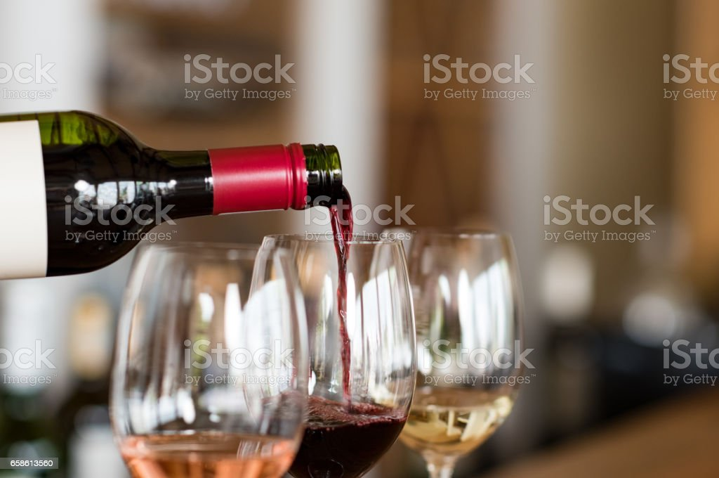 Pouring wine in glasses stock photo