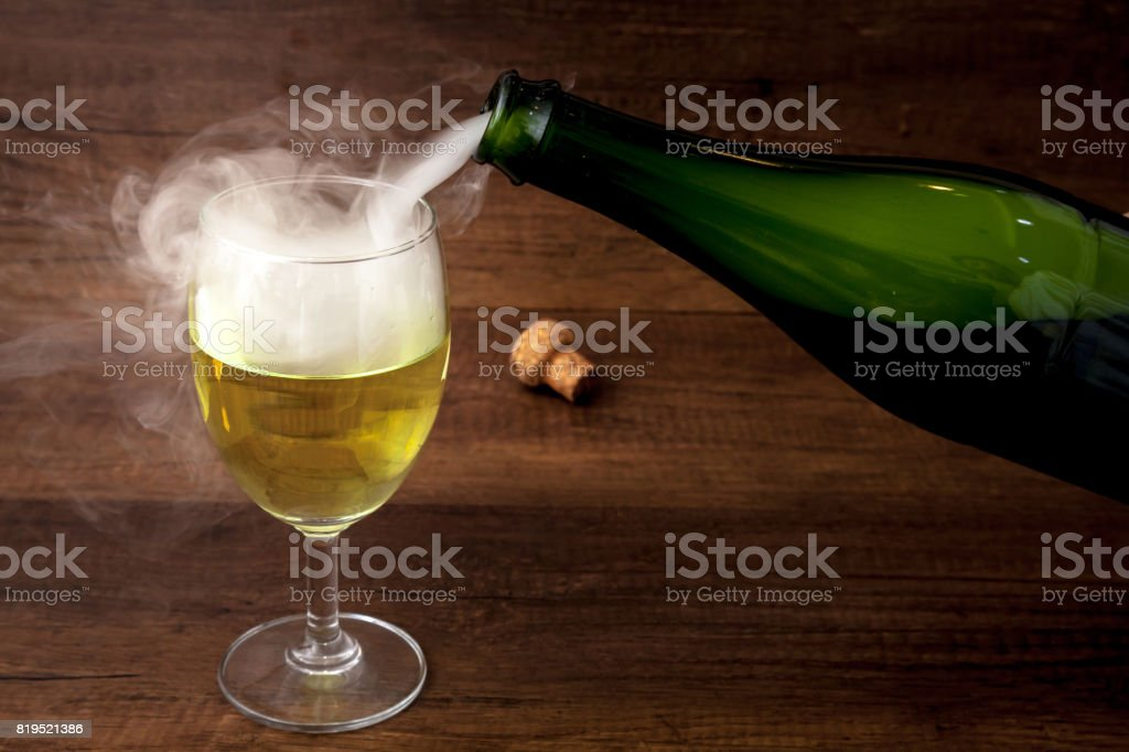 Pouring wine or champagne from the green bottle into the wine glass with some smoke on wooden background, for celebration or party stock photo