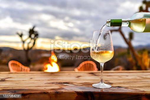 Pouring Wine with Desert Sunset and Fire Pit Backdrop