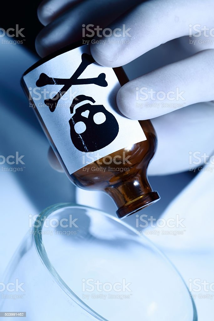 Pours poison into a glass gloved hand stock photo