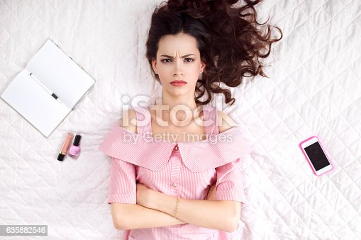 istock Pouted woman lying with crossed hands top view 635882546