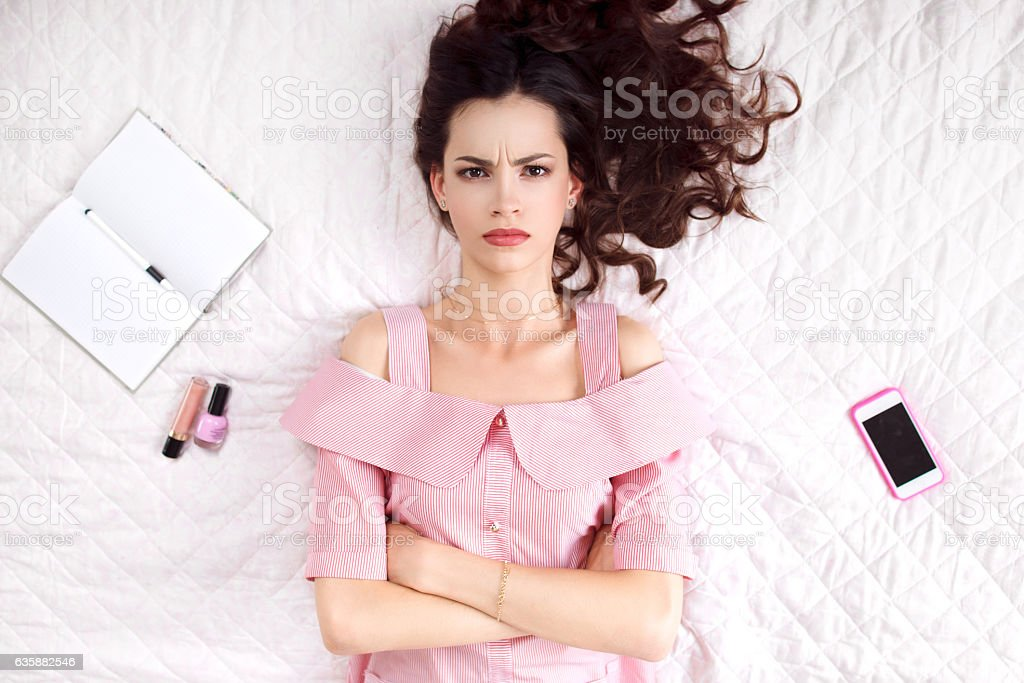 Pouted woman lying with crossed hands top view stock photo
