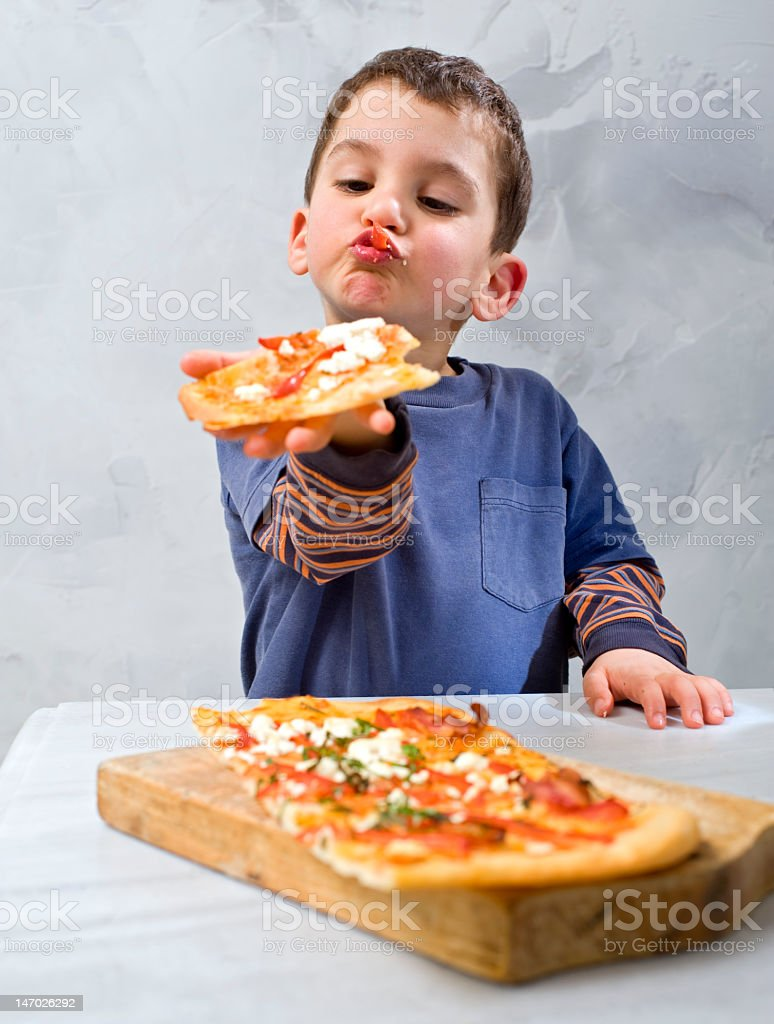 Pouting boy holding out a piece of pizza from his plate stock photo