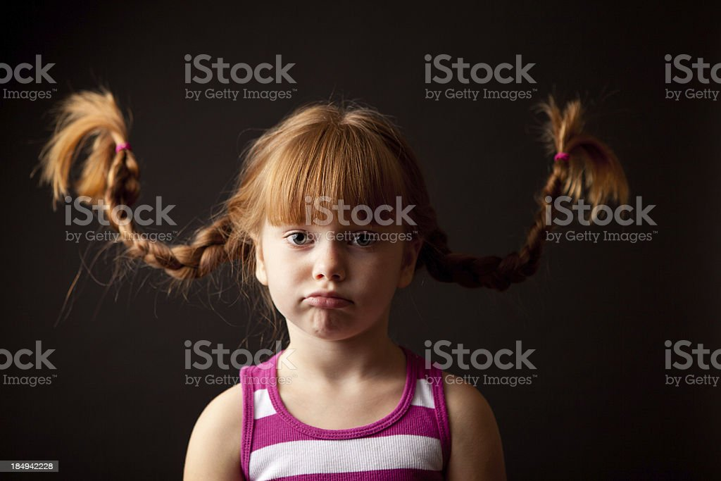 Pouting, Red-Haired Girl with Upward Braids, Isolated on Black royalty-free stock photo