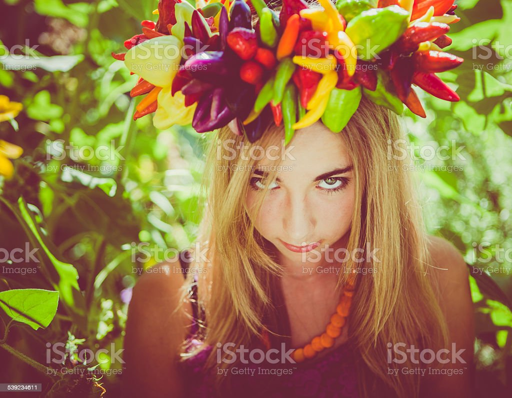 Pouting teen girl in garden & wearing fresh pepper wreath royalty-free stock photo