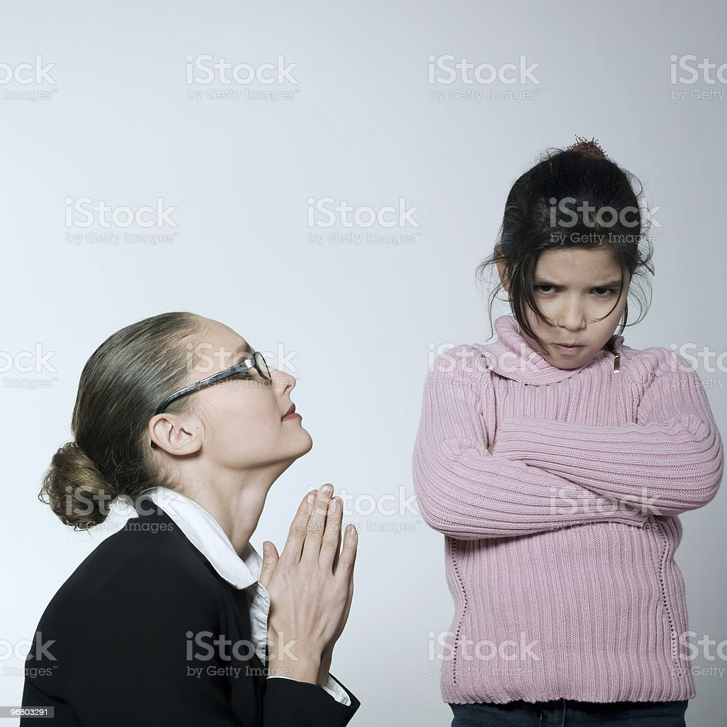 A pouty young girl in a pink sweater and a begging woman stock photo