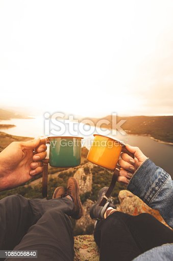 Pov image of couple holding enamel cups on mountain peak
