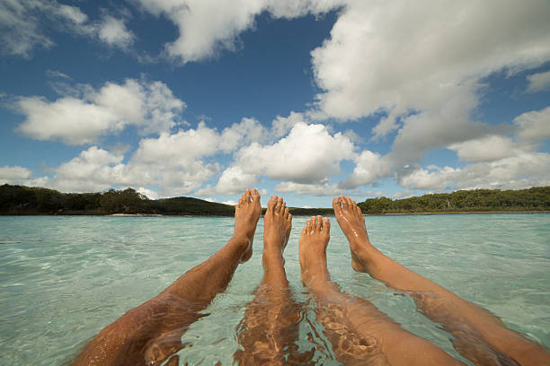 pov of a young couple bathing in the lake - woman leg beach pov stock photos and pictures