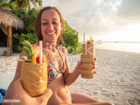 Personal perspective of man cheering with woman and drink at sunset