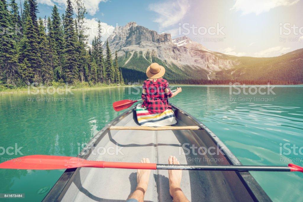 Pov of couple paddling red canoe on turquoise lake stock photo