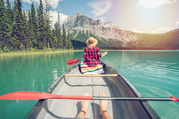 Pov of couple paddling red canoe on turquoise lake stock photo