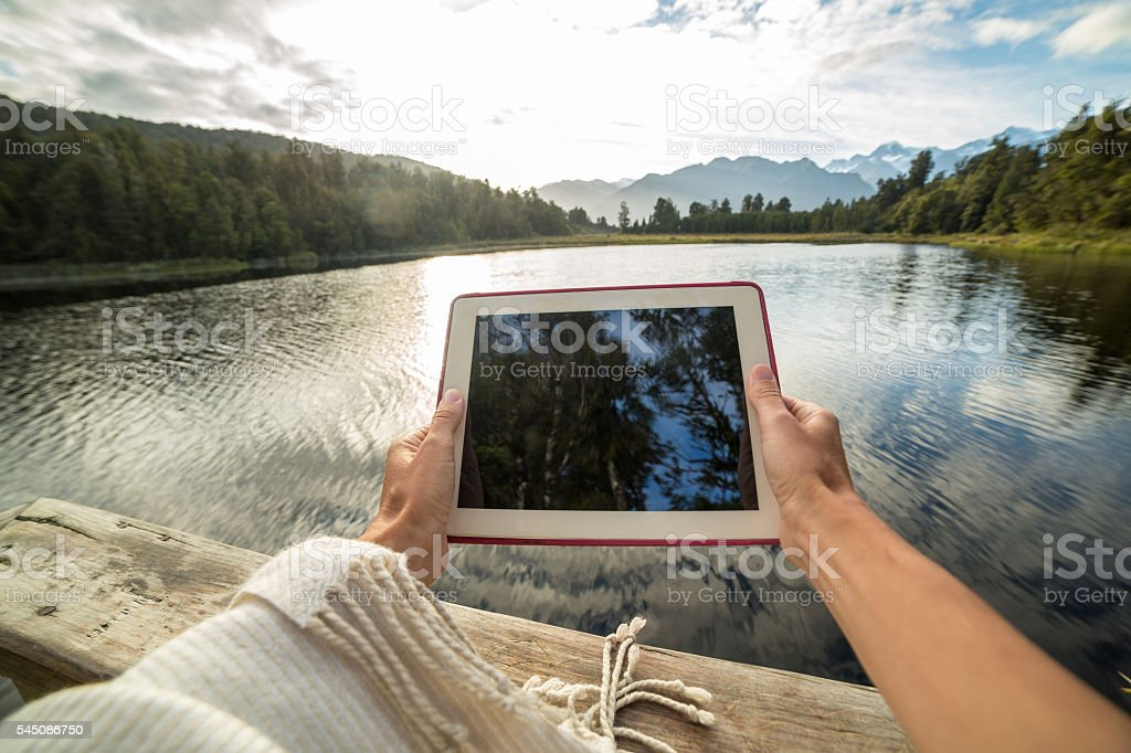 Woman takes a picture of the mountain lake landscape using a digital...