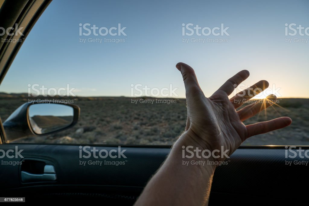 Pov of woman in car stretching out hand by the window to catch the sunrise royalty-free stock photo