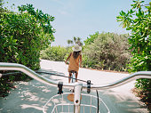 Pov point of view of couple cycling on tropical island. Personal perspective of person cycling with girlfriend in front. Tropical luxury vacations