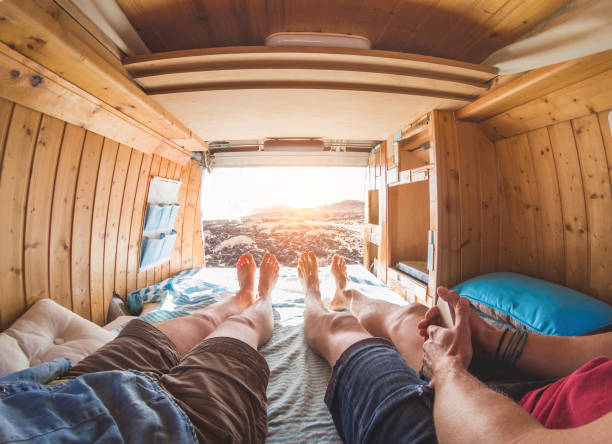 pov view of happy couple inside minivan at sunset - young people having fun on summer vacation - travel,love and nature concept - focus on feet - warm contrast filter - woman leg beach pov stock photos and pictures
