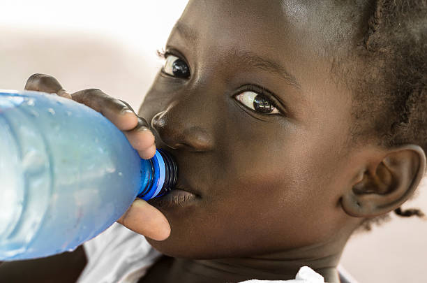 Poverty Symbol: African Black Girl Drinking Heathy Fresh Water stock photo