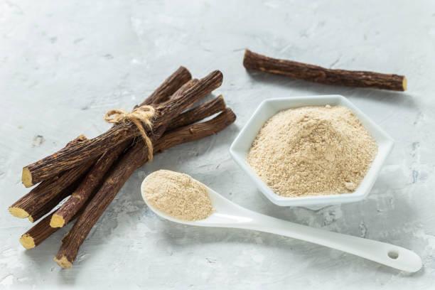 powder and licorice root on the table - glycyrrhiza glabra. - liquirizia foto e immagini stock