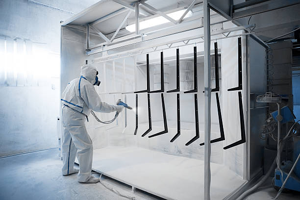 Powder coating  in a special camera Worker wearing protective wear performing powder coating of metal details in a special industrial camera face powder stock pictures, royalty-free photos & images