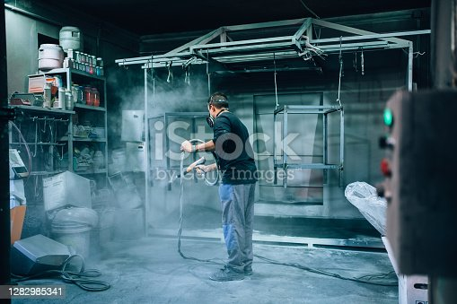 Man with protective mask sprays powder paint from a gun on metal products in the workshop.