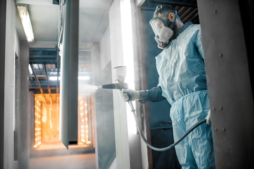 Painter in protective wear paints metal products with powder paint. Powder coating process at the manufacturing. High quality photo