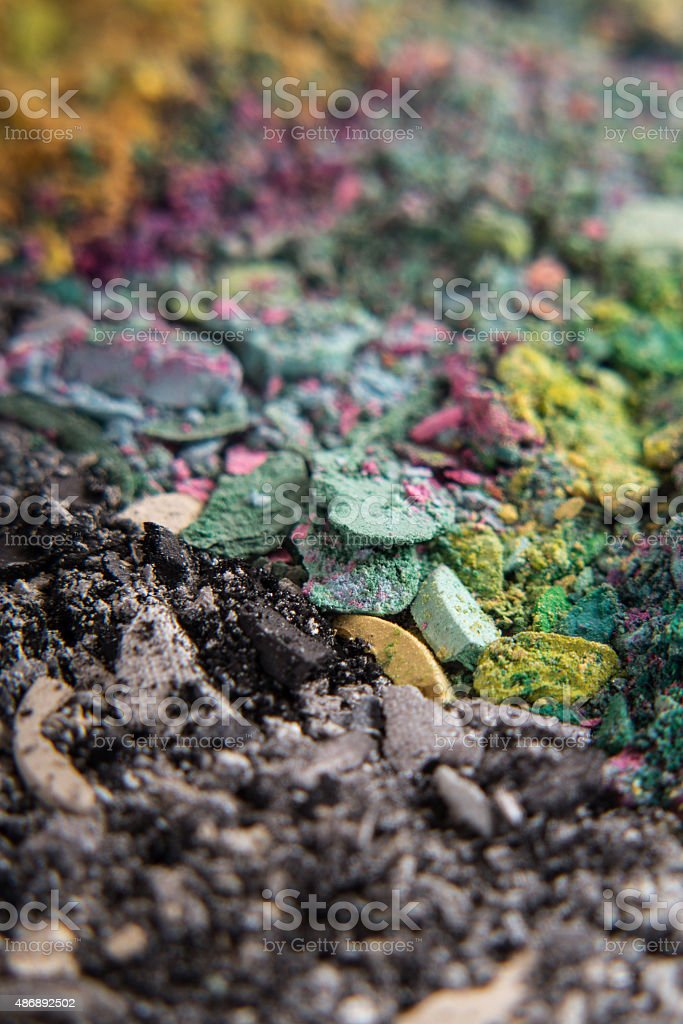 powder crumbs of eyeshadow in color next to black grey stock photo