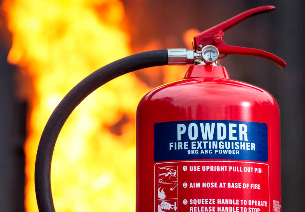 ABC Powder Fire Extinguisher with flames behind stock photo