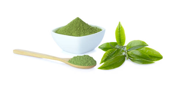 Powder green tea in cup with wooden spoon and green tea leaf on white background and clipping path stock photo