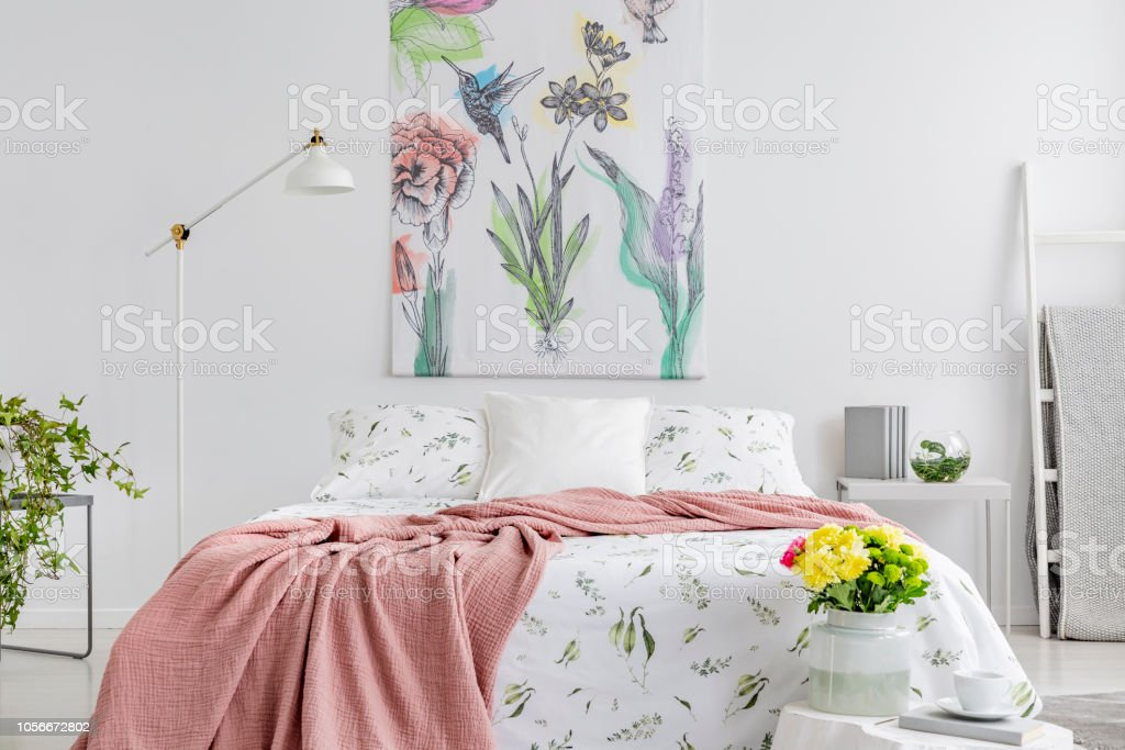Powder pink blanket thrown on king-size bed with floral bedding in...