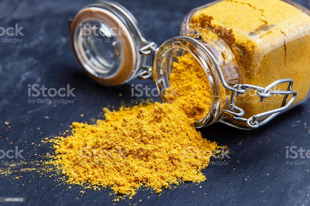 powder seasoning spice turmeric on a black stone stock photo