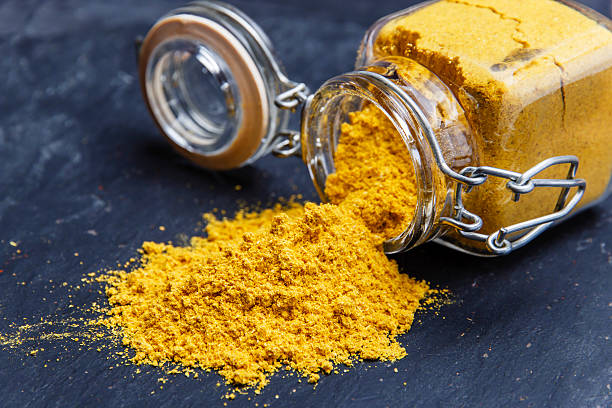 powder seasoning spice turmeric on a black stone powder seasoning spice turmeric on a black stone curry powder stock pictures, royalty-free photos & images