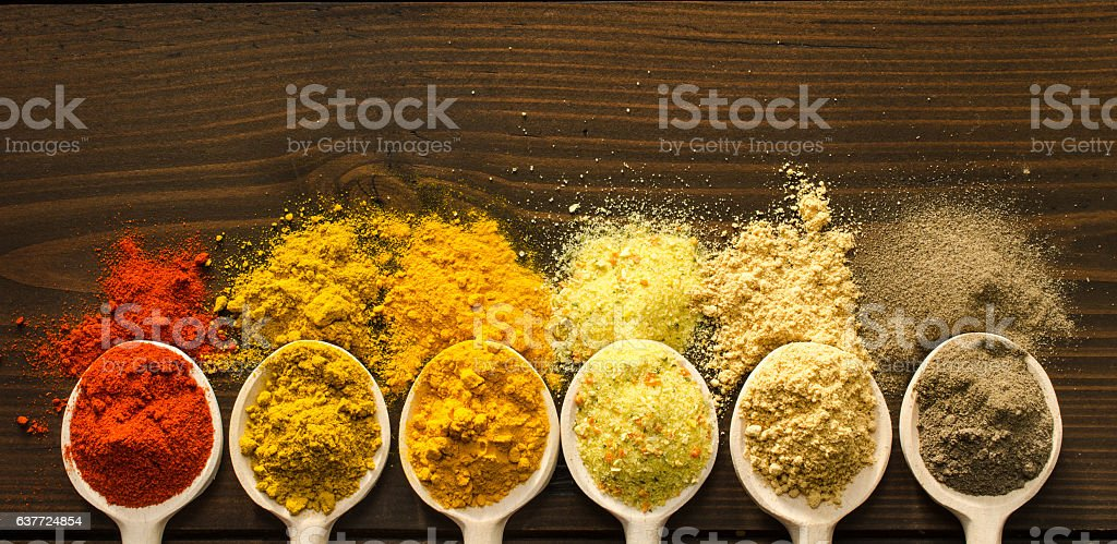 Powder spices and wooden spoons on wooden table stock photo
