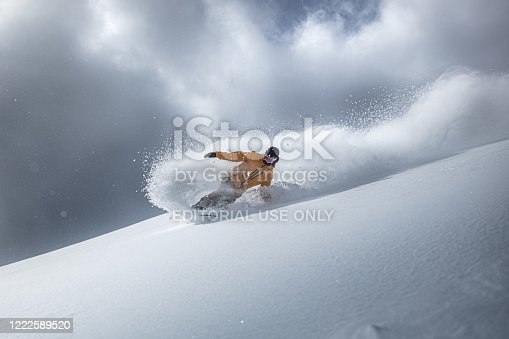Professional snowboarder making a turn in powder snow at strandafjellet, Norway.