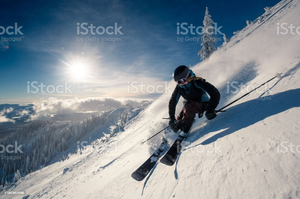 powder turns female skier on ski slope British Columbia Stock Photo