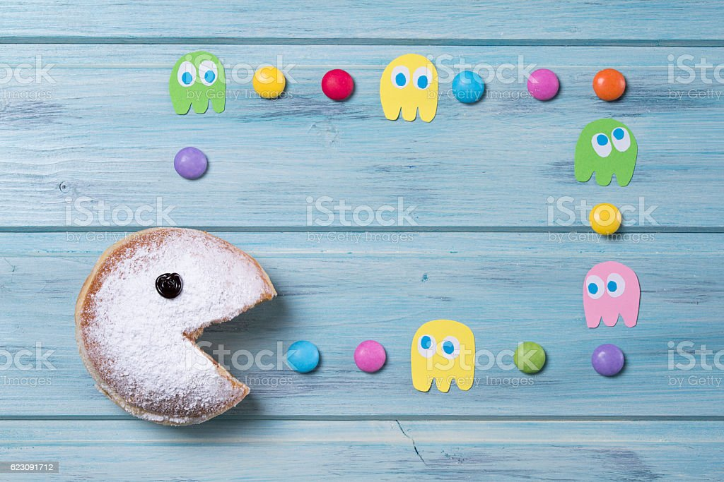 Powdered donut with smiley face and colored smarties stock photo