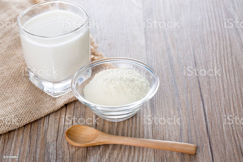 Cup of milk and powdered milk on the table.