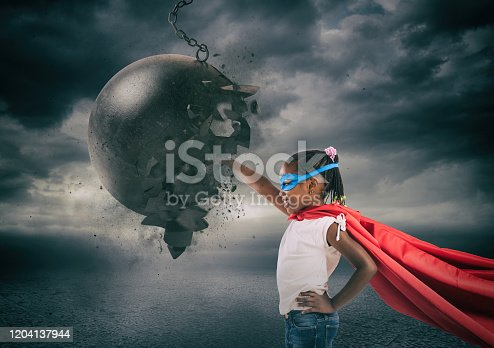 istock Power and determination of a super hero child against a wrecking ball 1204137944