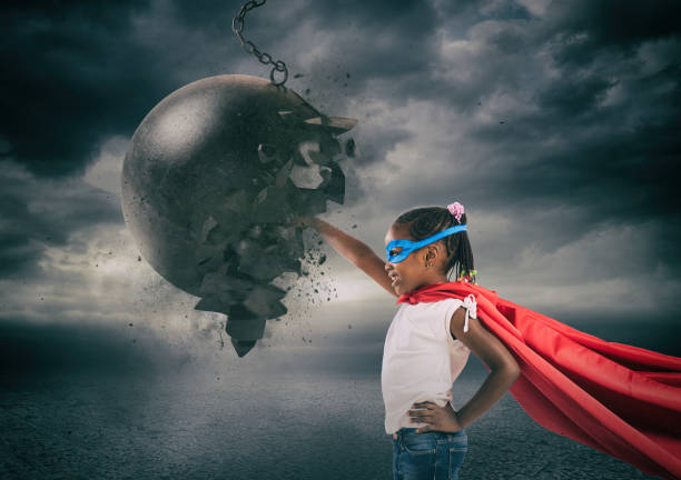Power and determination of a super hero child against a wrecking ball stock photo