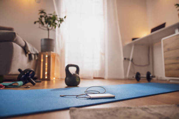 Power bank on yoga mat in living room with exercise equipmen, chargingt stock photo