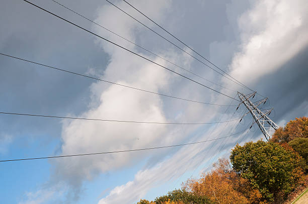 power cable dangles across dominant grey and blue autumn sky stock photo