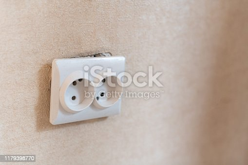 istock AC power double socket on wall, bad incorrectly installed, copy space. Socket for europlug type. Violations of safety standards. Fire-hazard. 1179398770
