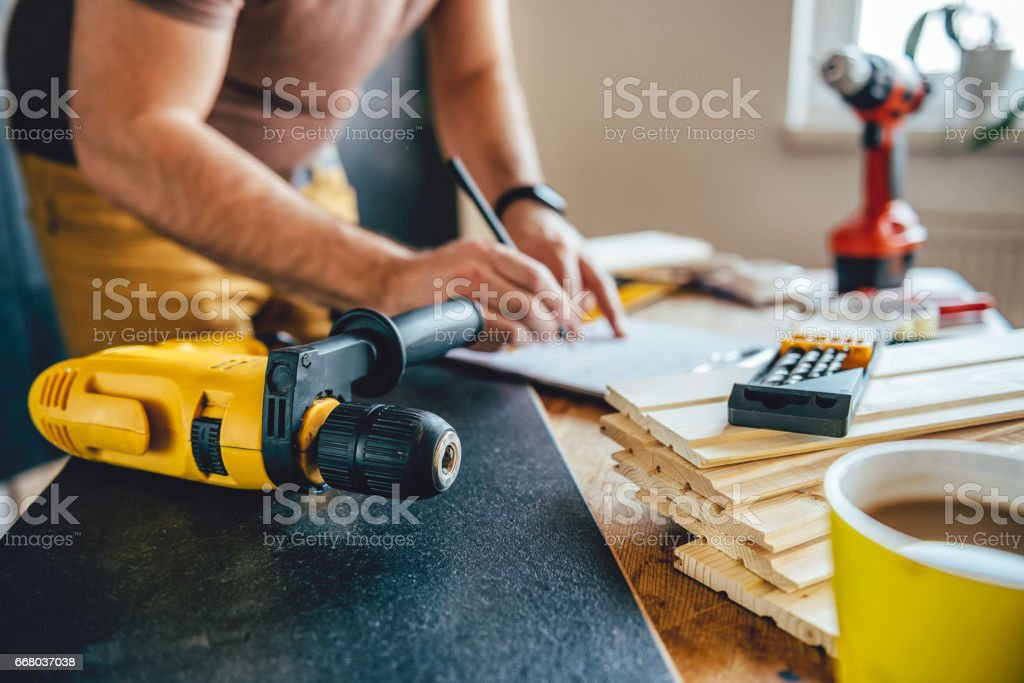 Power drill and Man making draft plan in the background stock photo