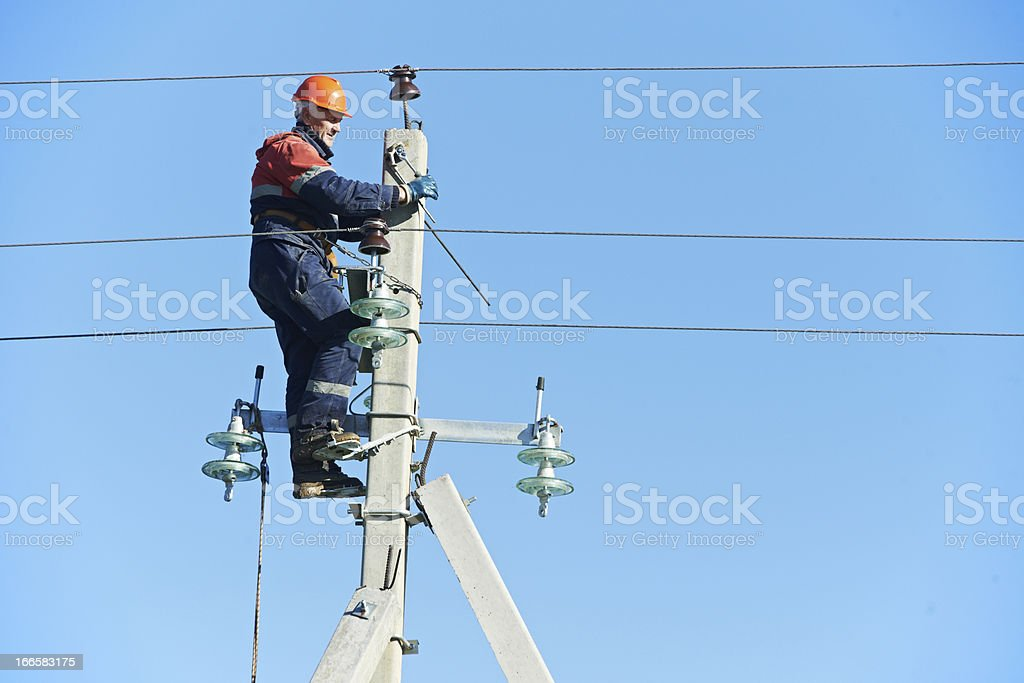 power electrician lineman at work on pole Electrician lineman repairman worker at climbing work on electric post power pole Adult Stock Photo