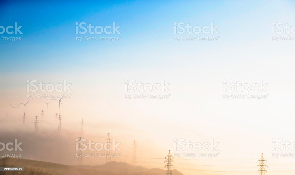 Power Generating Windmills and Electricity pylon stock photo