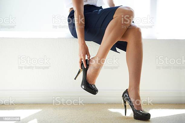 Closeup of a businesswoman putting on a pair of heels