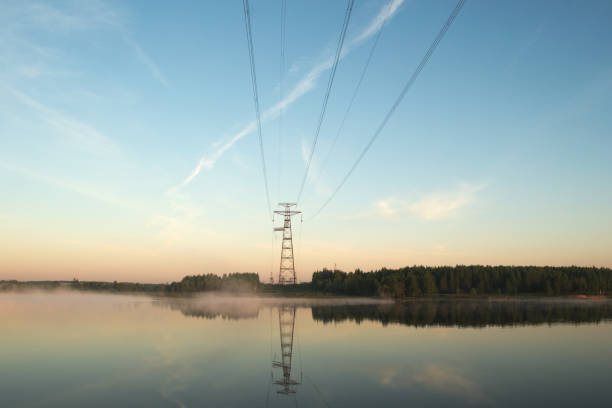 Power line crosses the river stock photo