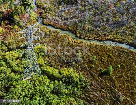 Aerial drone view of a high voltage power line crossing a wetland area.