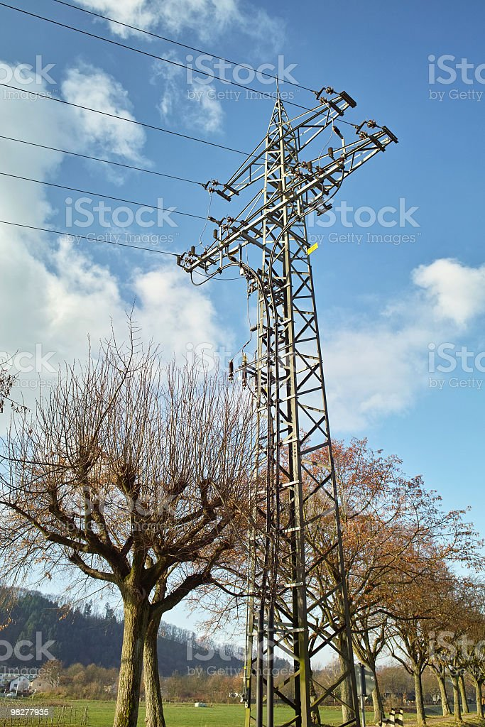 power line in front of blue sky with trees royalty-free stock photo