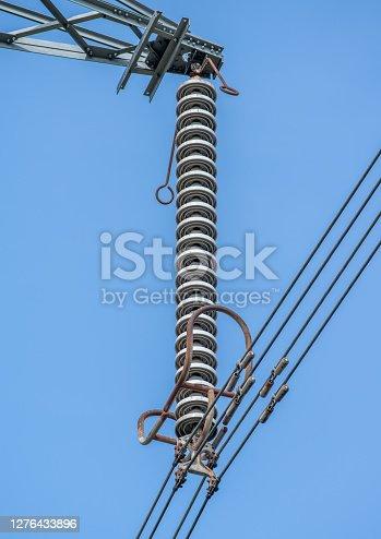 A single power line insulator on electricity pylon with blue sky background.