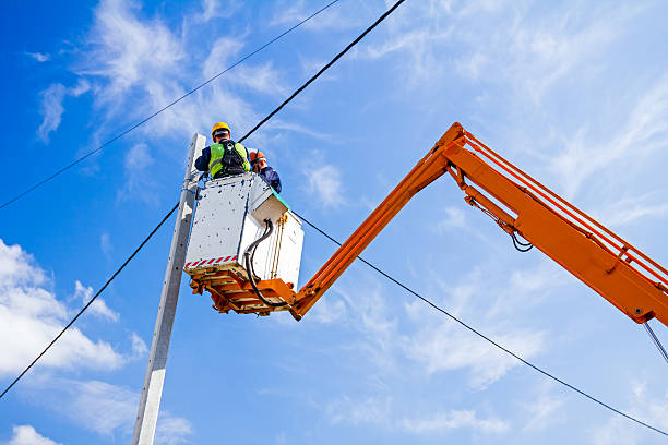Power line team at work on a pole Technician works in a bucket high up on a power pole. retrieving stock pictures, royalty-free photos & images